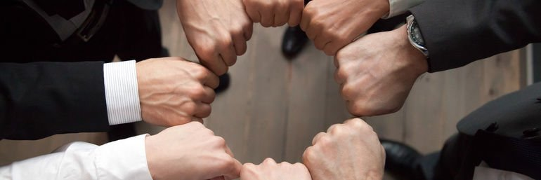 Top_above_close_up_view_group_of_businessmen_in_formal_suits_standing_putting_hands_fists_in_circle_shape._Teamwork_trust_motivation_support_concept,_horizontal_photo_banner_for_website_header_design