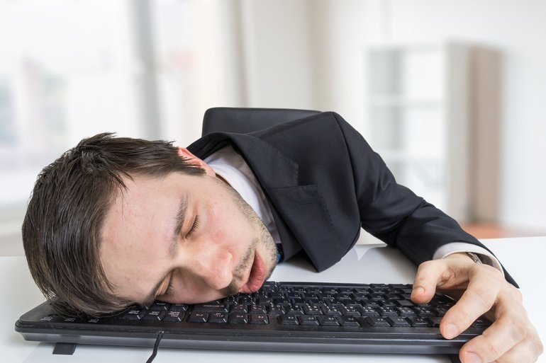 Exhausted_or_tired_businessman_is_sleeping_on_keyboard_in_office.