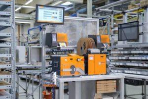 Das Weidmüller Wire Processing Center (WPC) auf einem kompakten fahrbaren Werktisch schließt mit aufeinander abgestimmten Komponenten – Abläng-, Abisolier- und Crimpautomat, Thermotransferdrucker und Kabelzuführungen – die logistische Lücke zwischen Vollautomatisierung und Handarbeit.